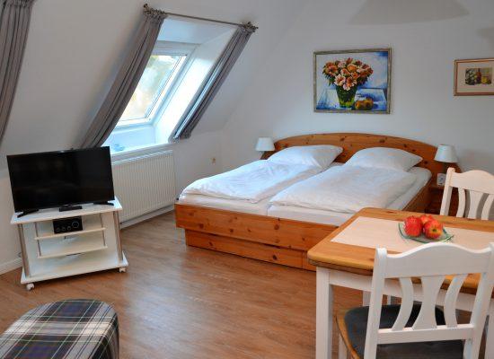 Das mit Liebe eingerichtete Appartement mit dem Schlafbereich im Hintergrund